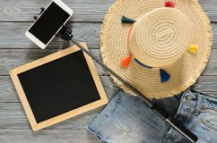 Womens clothing, accessories denim shorts, straw hat, cellphone. Womens clothing; accessories denim shorts; straw hat; cellphone; selfie stick; chalkdoard on Royalty Free Stock Photography