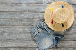 Womens clothing, accessories denim shorts, straw hat on grey w. Ooden background with copy space. Trendy fashion outfit. Shopping concept. Mock up for online Stock Photo