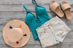 Womens clothing, accessories denim shorts, straw hat, swimsuit,. Sandals on grey wooden background. Trendy fashion outfit. Shopping, travel, summer, beach Royalty Free Stock Images