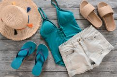 Womens clothing, accessories denim shorts, straw hat, swimsuit,. Sandals on grey wooden background. Trendy fashion outfit. Shopping, travel, summer, beach Royalty Free Stock Photography