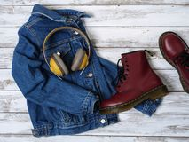 Womens clothing, accessories, footwear burgundy boots, yellow wireless headphones, denim jacket. Fashion outfit. Shopping. Concept. Flat lay royalty free stock image