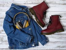 Womens clothing, accessories, footwear burgundy boots, yellow wireless headphones, denim jacket. Fashion outfit. Shopping. Concept. Flat lay royalty free stock images