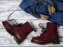 Womens clothing, accessories, footwear burgundy boots, yellow wireless headphones, denim jacket. Fashion outfit. Shopping. Concept. Flat lay royalty free stock photo