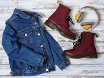 Womens clothing, accessories, footwear burgundy boots, yellow wireless headphones, denim jacket. Fashion outfit. Shopping. Concept. Flat lay stock photo