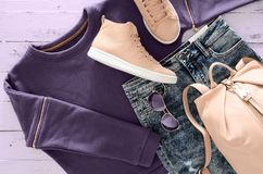 Womens clothing, accessories, footwear violet sweatshirt, acid. Washed jeans,  leather backpack and sneakers, sunglasses on wooden background. Outfit for teens Royalty Free Stock Image