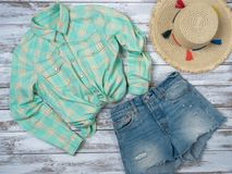 Womens clothing, accessories plaid shirt, denim shorts, straw hat. Fashion outfit, spring summer collection. Shopping concept. Flat lay, top down view royalty free stock image