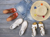 Womens clothing, accessories, shoes denim shorts, straw hat, sandals, sneakers. Fashion outfit, spring summer collection. royalty free stock images