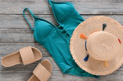 Womens clothing, accessories, shoes straw hat, blue green swims. Uit, sandals on grey wooden background. Trendy fashion outfit. Shopping, travel, summer, beach Stock Images