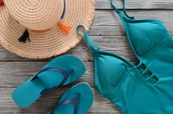 Womens clothing, accessories, shoes straw hat, blue green swims. Uit, flip flops on grey wooden background. Trendy fashion outfit. Shopping, travel, summer Royalty Free Stock Photos