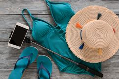 Womens clothing, accessories, shoes straw hat, blue green swims. Uit, flip flops, cellphone, selfie stick on grey wooden background. Trendy fashion outfit Royalty Free Stock Images