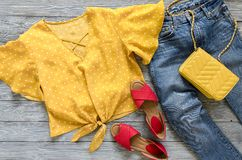 Womens clothing, accessories, shoes yellow blouse in polka dot,. Blue jeans, leather red sandals,  yellow crossbody bag. Fashion outfit. Shopping concept. Flat Royalty Free Stock Images