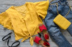 Womens clothing, accessories, shoes yellow blouse in polka dot,. Blue jeans, leather red sandals,  yellow crossbody bag, lipstick. Fashion outfit. Shopping Royalty Free Stock Photos