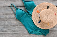 Womens clothing, accessories straw hat, blue green swimsuit on. Grey wooden background with copy space. Trendy fashion outfit. Shopping, travel, summer, beach Royalty Free Stock Photography