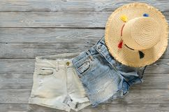 Womens clothing, accessories two denim shorts, straw hat on gr. Ey wooden background with copy space. Trendy fashion outfit. Shopping concept. Mock up for online Stock Photography
