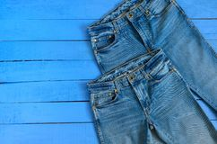 Womens clothing blue jeans on blue wooden background with copy. Space. Fashion outfit. Shopping concept. Top view Royalty Free Stock Photo