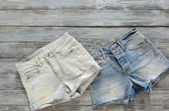 Womens clothing denim shorts on grey wooden background with co. Py space. Trendy fashion outfit. Shopping concept. Mock up for online store.  Flat lay. Summer Royalty Free Stock Photography