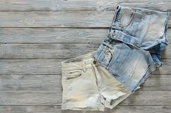 Womens clothing denim shorts on grey wooden background with co. Py space. Trendy fashion outfit. Shopping concept. Mock up for online store.  Flat lay. Summer Royalty Free Stock Photos
