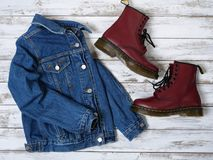 Womens clothing, footwear burgundy boots, denim jacket. Fashion outfit. Shopping concept. Flat lay. Womens clothing, footwear burgundy boots, denim jacket royalty free stock image