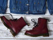 Womens clothing, footwear burgundy boots, denim jacket. Fashion outfit. Shopping concept. Flat lay stock image