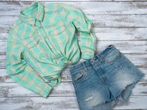 Womens clothing plaid shirt, denim shorts. Fashion outfit, spring summer collection. Shopping concept. Flat lay, top down view stock photography