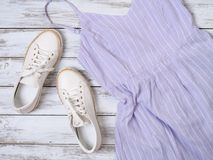 Womens clothing, shoes, accessories lavender dress, white leather sneakers. Fashion outfit, spring summer collection. Shopping. Concept. Flat lay, view from stock image