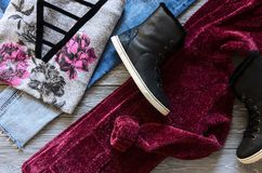 Womens clothing and shoes black real leather high top sneakers,. Blue jeans, burgundy velvet cardigan and sweater. Wish list or shopping overview, fashion look Stock Photo