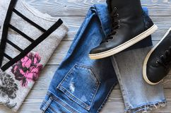 Womens clothing and shoes black real leather high top sneakers,. Blue jeans, burgundy velvet cardigan and sweater. Wish list or shopping overview, fashion look Royalty Free Stock Photography