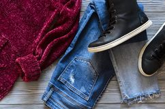Womens clothing and shoes black real leather high top sneakers,. Blue jeans, burgundy velvet cardigan and sweater. Wish list or shopping overview, fashion look Royalty Free Stock Images