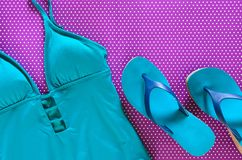 Womens clothing, shoes blue green swimsuit, flip flops on viol. Et background in polka dots. Trendy fashion outfit. Shopping, travel, summer, beach concept Stock Photos