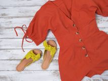 Womens clothing, shoes yellow leather sandals with knotted bow, linen button front romper. Fashion outfit, spring summer. Collection. Shopping concept. Flat lay royalty free stock photo