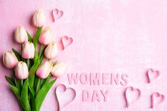 Womens day concept. Pink tulips and paper hearts with Wooden letters forming word Womens day written on pink and white wooden. Background stock photography