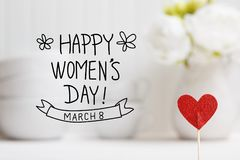 Womens Day message with small red heart. With white dishes Stock Photos