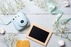 Womens desk with photo camera, picture frame, cookies. Spring minimal flowers frame, pastel colors, flat lay style, top view. Beau. Ty technology concept stock photo