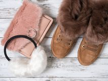Womens fashion accessories, shoes suede sneakers, crossbody bag, white fur earmuffs. Shopping concept. Flat lay. Winter. Collection stock images