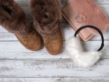 Womens fashion accessories, shoes suede sneakers, crossbody bag, white fur earmuffs. Shopping concept. Flat lay. Winter. Collection royalty free stock images