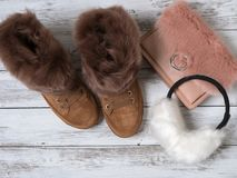 Womens fashion accessories, shoes suede sneakers, crossbody bag, white fur earmuffs. Shopping concept. Flat lay. Winter. Collection stock photo