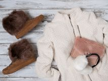 Womens fashion clothes, accessories, shoes plush jacket, suede sneakers, crossbody bag, white fur earmuffs. Shopping concept. Flat lay. Winter collection stock photography