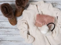 Womens fashion clothes, accessories, shoes plush jacket, suede sneakers, crossbody bag, white fur earmuffs. Shopping concept. Flat lay. Winter collection royalty free stock images