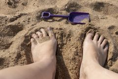 A Persons Feet In The Sand. A womens feet with a small purple spade in front for her on the beach sand on a sunny summers day stock photography