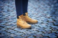 Womens feet in yellow boots Stock Photos