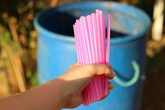 Women& x27;s hand holding pink plastic tube  To throw away the trash  Concepts of using plastic tubes to reduce global warming. Womens hand holding pink plastic stock image