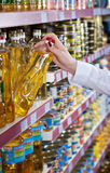 Womens hand selects the bottle of oil at the store Royalty Free Stock Image