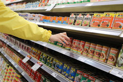 Womens hand selects the can food at the store Stock Image
