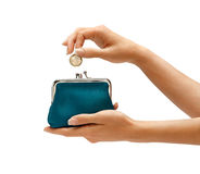 Womens hand throwing a coin one euro in the purse. Royalty Free Stock Photos