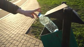 Womens hand throws an empty plastic bottle into the trash can.  stock footage