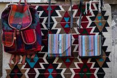 Womens handbags made of hand-made wool fabric hanging on the background of hand-woven carpet with traditional patterns. stock photo