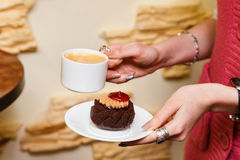 Womens hands hold a cup of coffee and cake Royalty Free Stock Photos