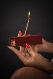 Womens hands ignite big matches for a tompus cigare or a firepla Royalty Free Stock Image