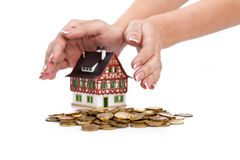 Womens hands protect miniature house with coins Stock Images