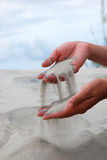 Womens hands with sand. A women's hands with sand at the beach Stock Photos